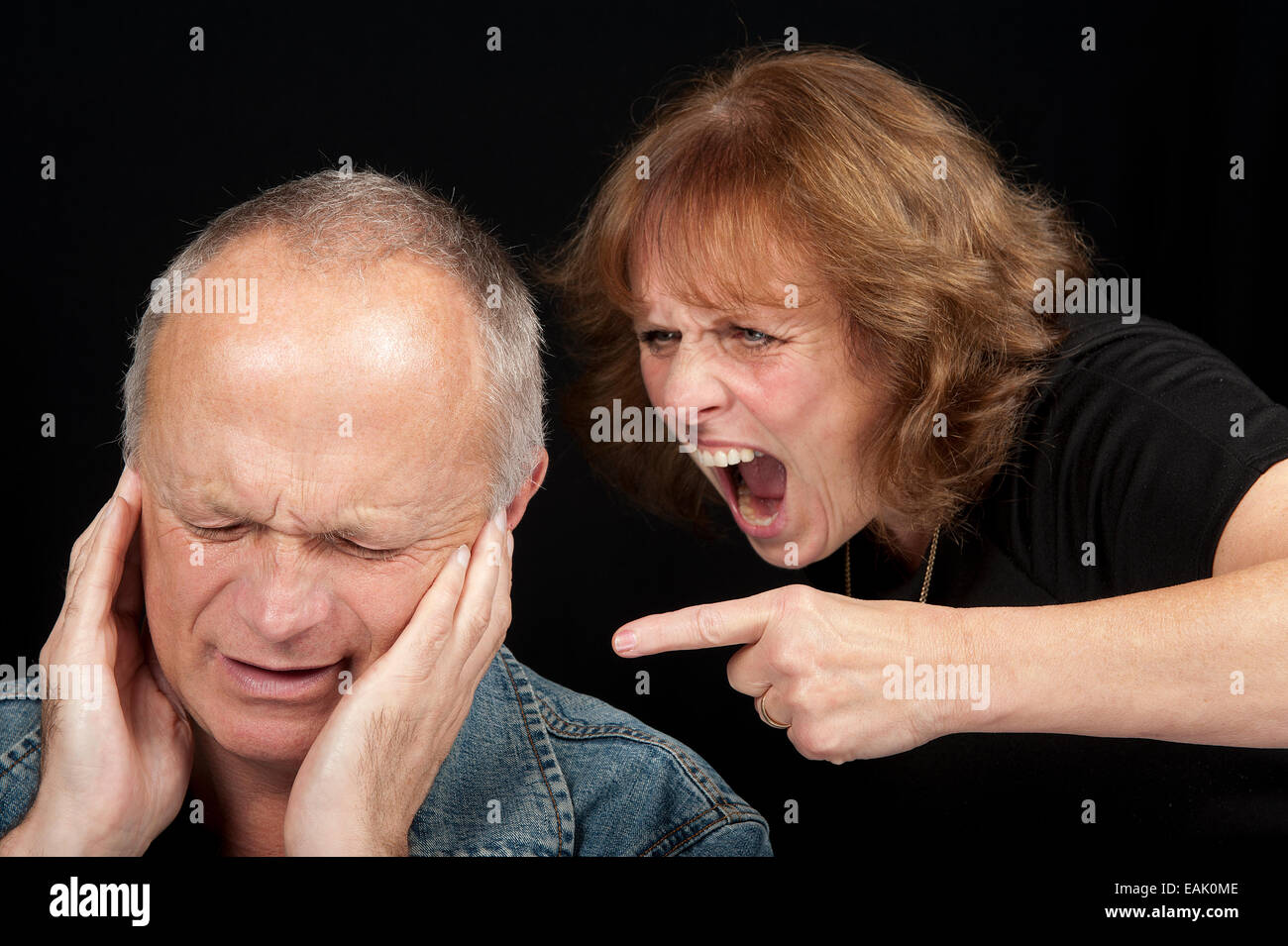 Middle aged couple having an argument, with the woman shouting and pointing finger at the crying man. - Stock Image