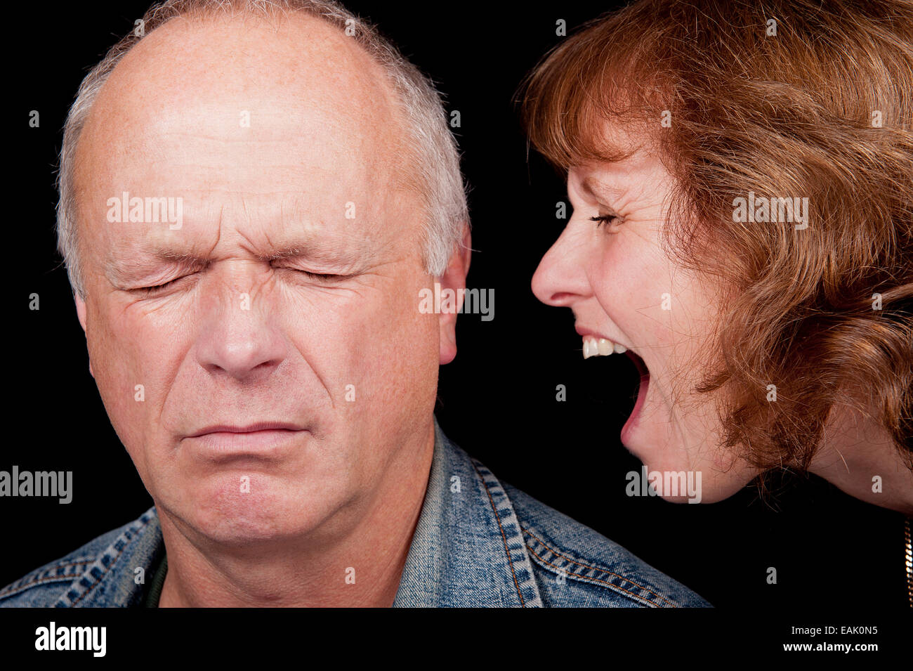 Middle aged couple having an argument, with the woman shouting at the man while he is crying. - Stock Image