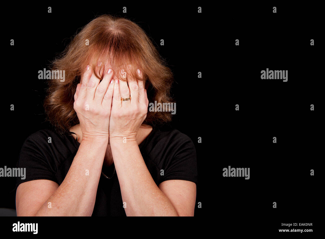 Middle aged woman covering her face with her hands, against a black background. - Stock Image