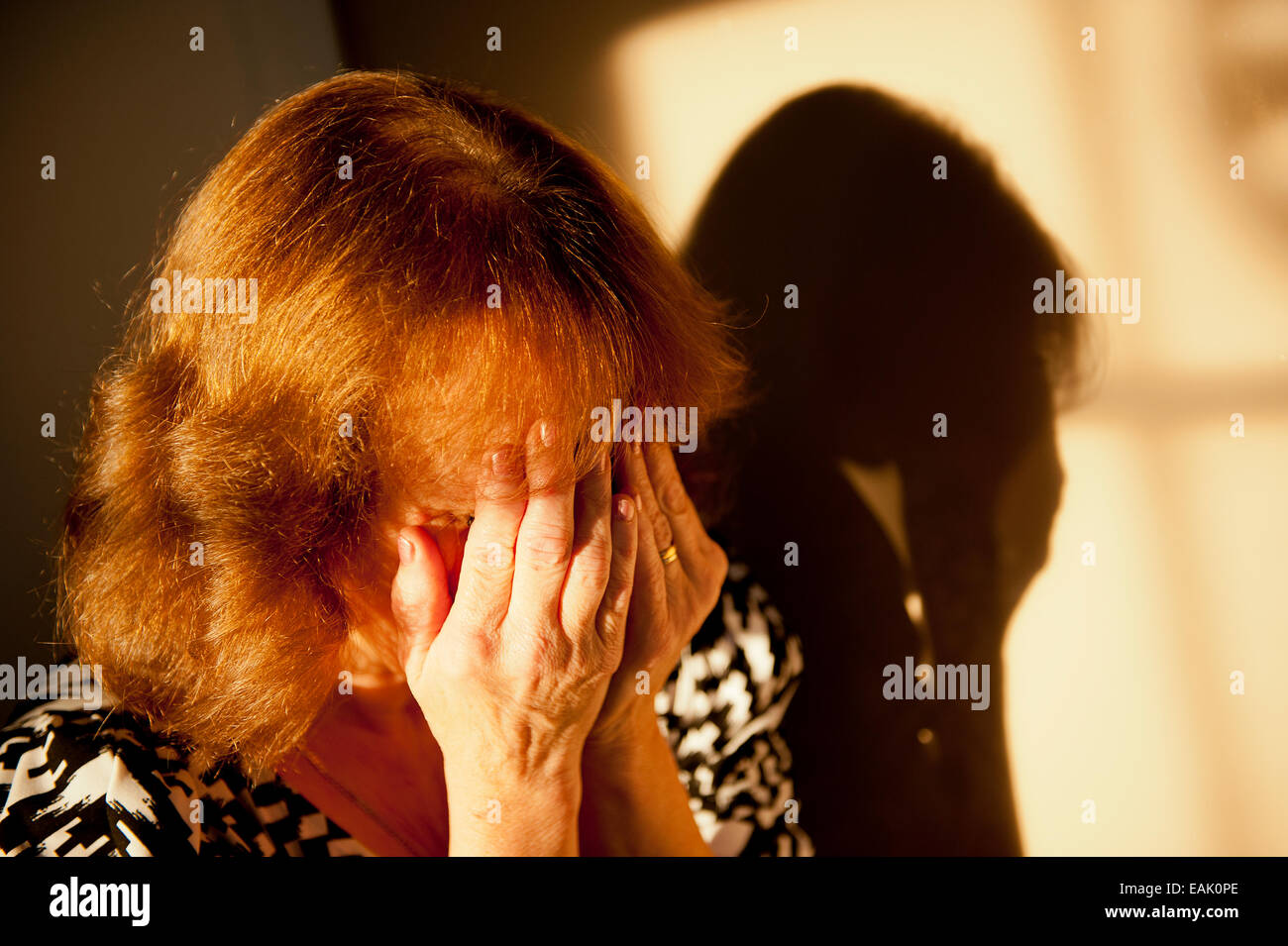 Tearful woman covering her face with both hands. - Stock Image