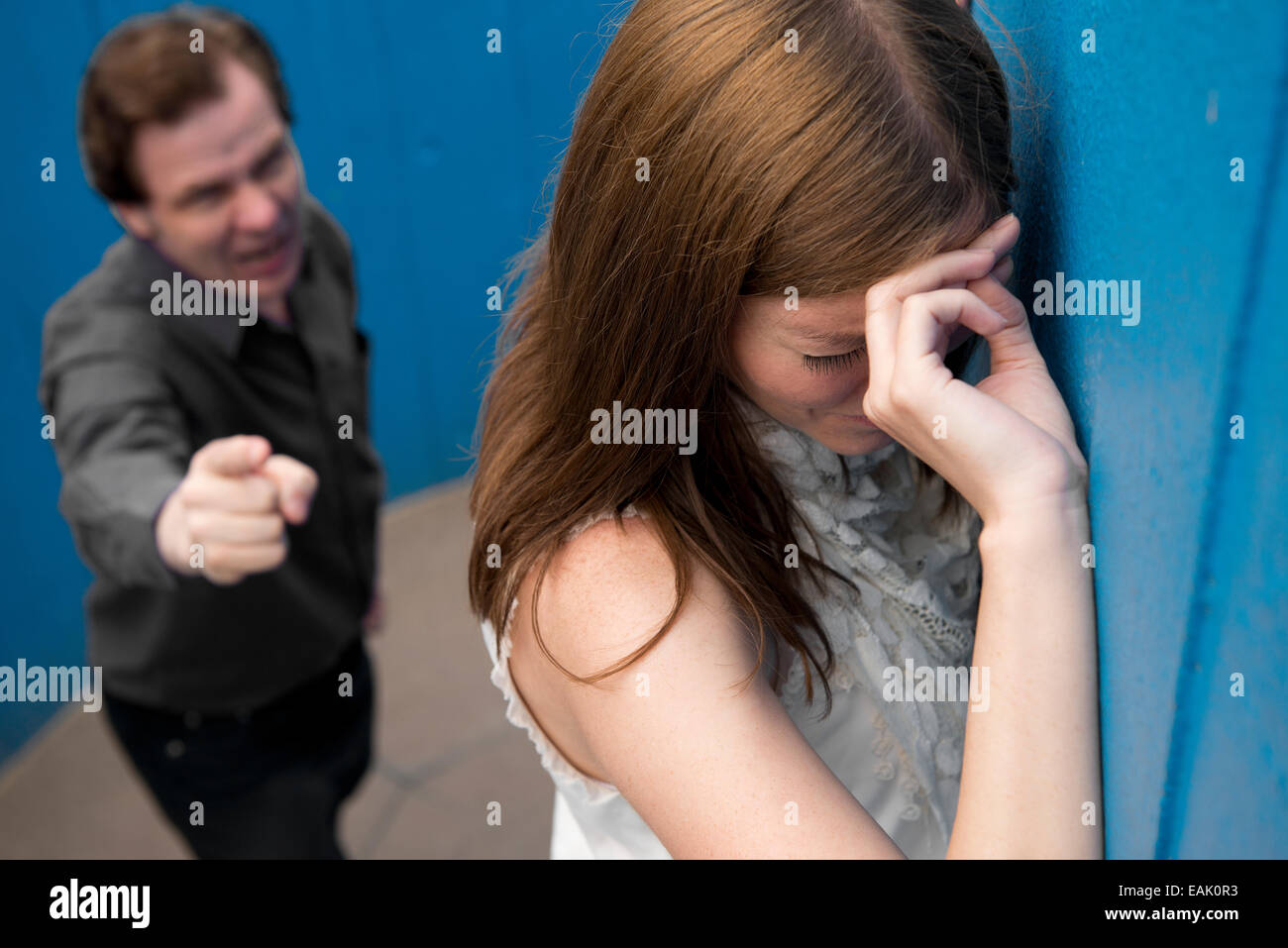 Tearful young woman in the foreground, with aggressive man, lower down in shot behind her. - Stock Image