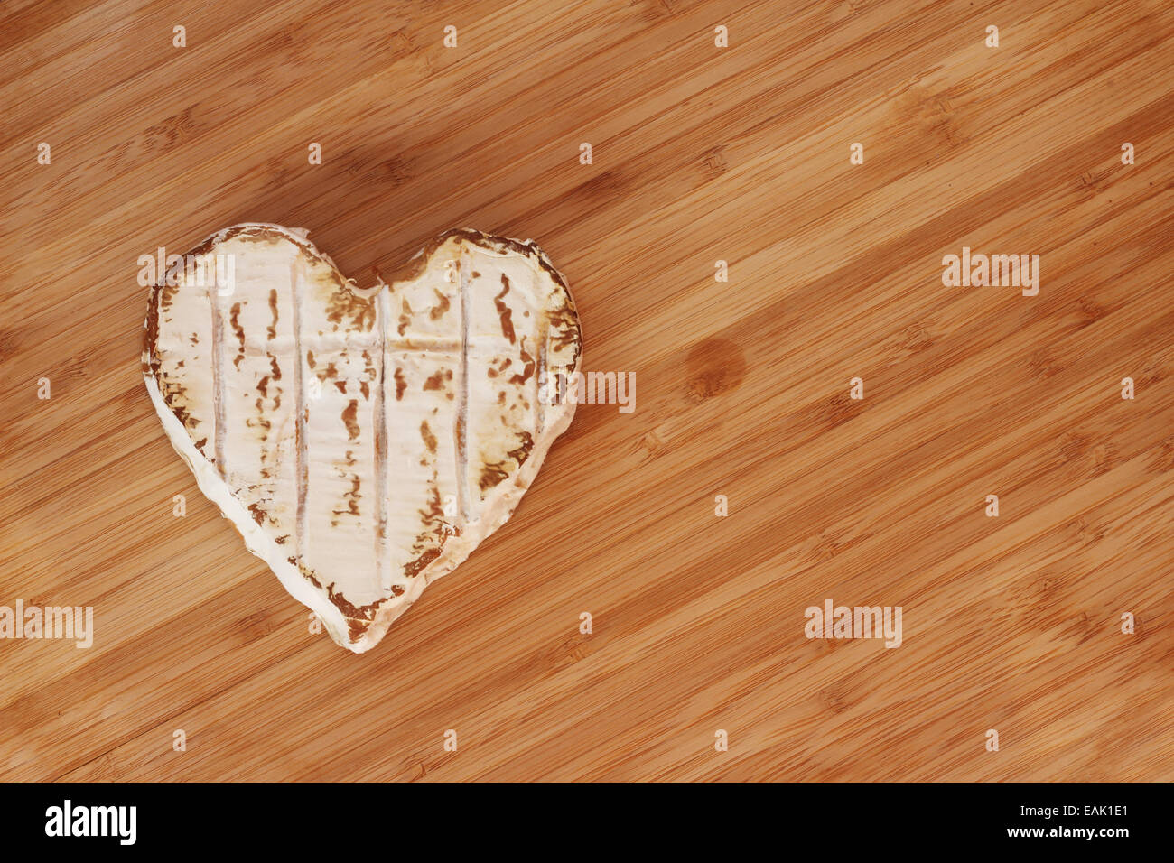 Neufchatel cheese shaped like heart on wooden cutting board - Stock Image
