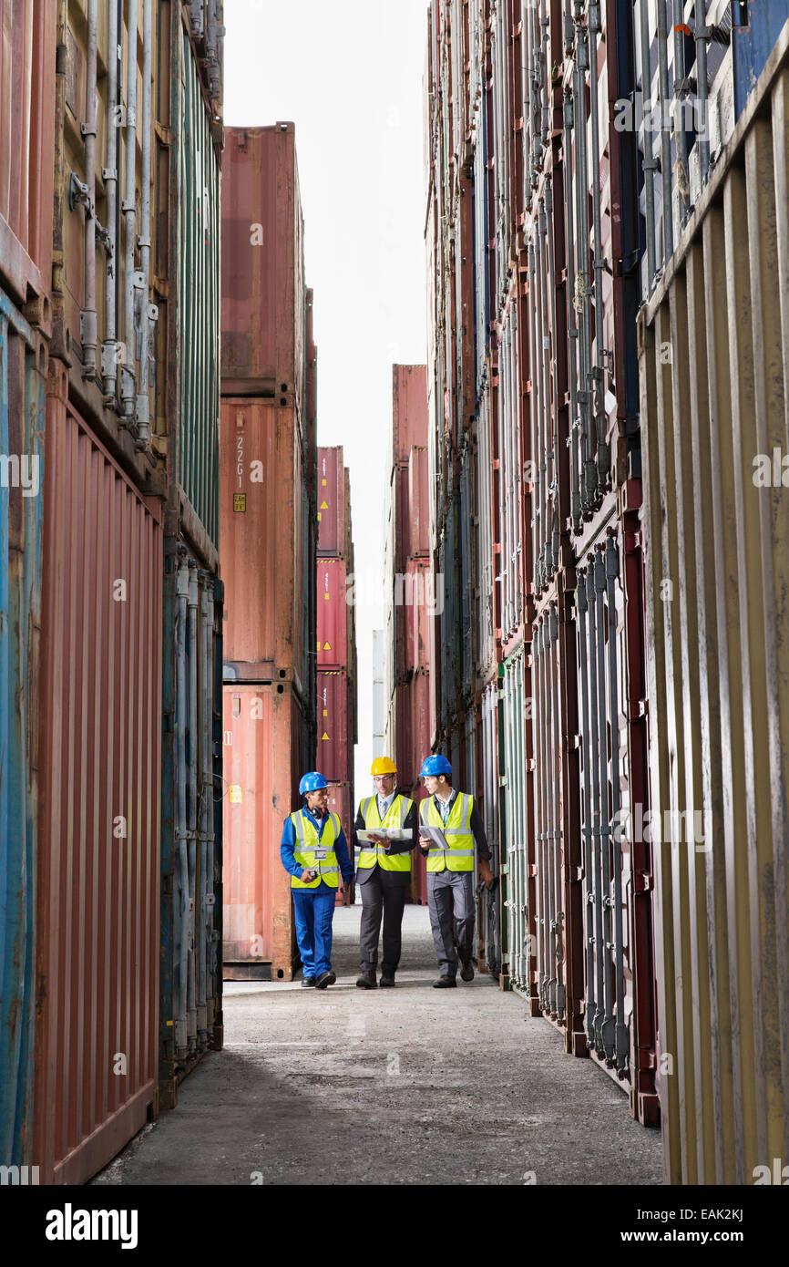 Workers talking between cargo containers - Stock Image