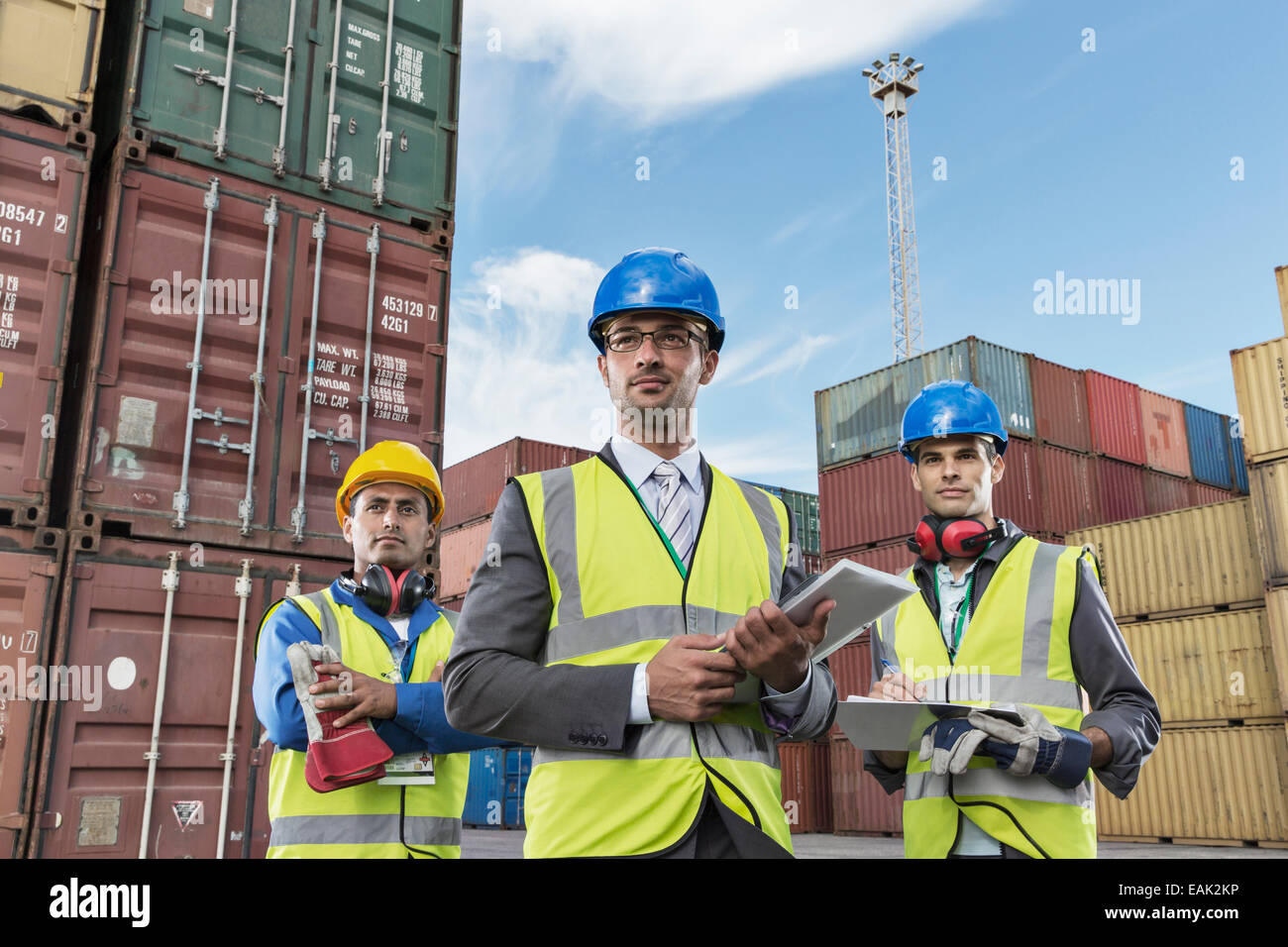 Businessmen wearing protective workwear near cargo containers - Stock Image