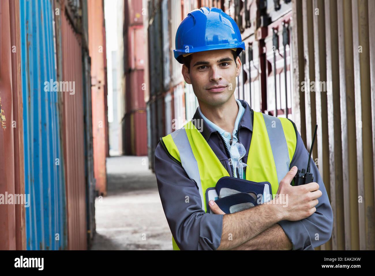 Worker standing between cargo containers Stock Photo