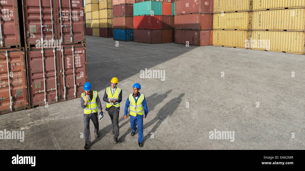 Businessmen and worker walking near cargo containers Stock Photo