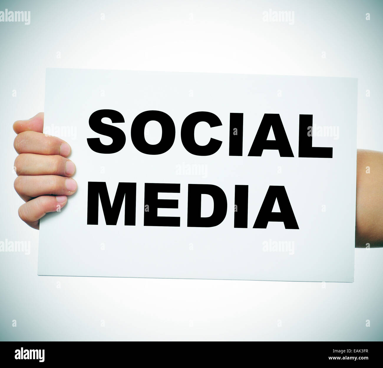 a man hand holding a signboard with the concept social media written in it - Stock Image