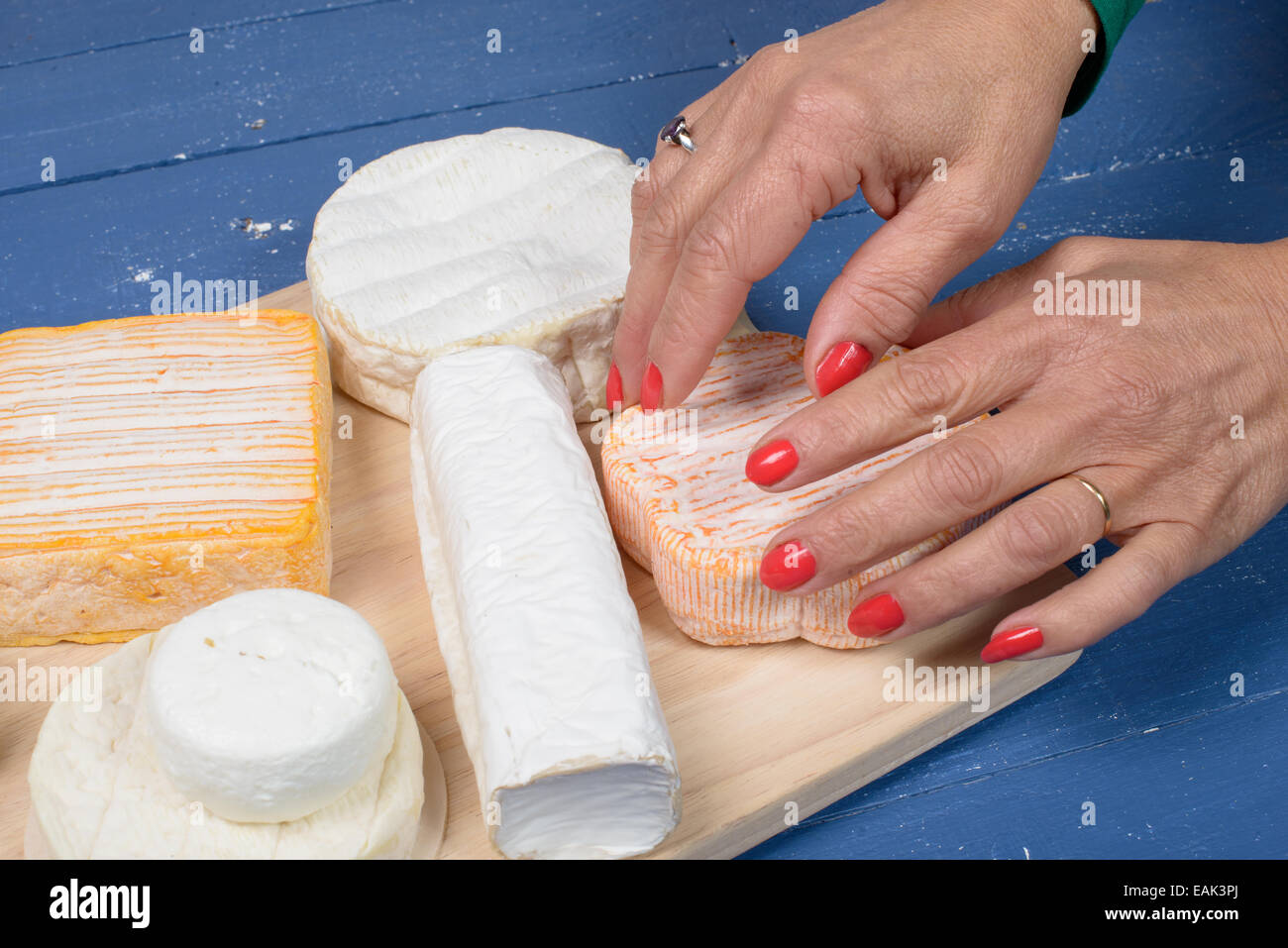 presentation of different French cheeses on blue table - Stock Image