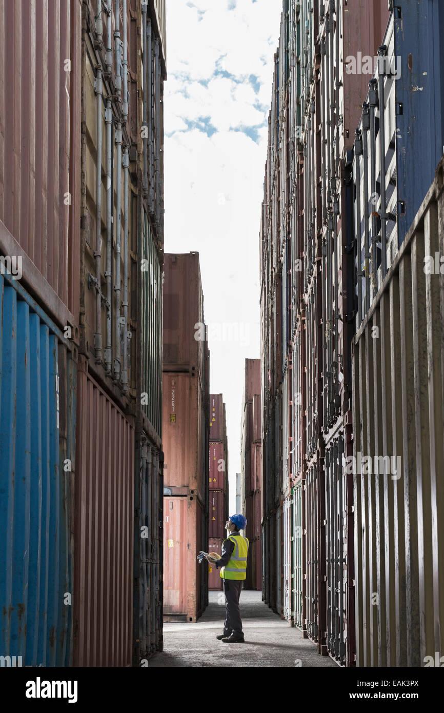 Worker standing between cargo containers - Stock Image