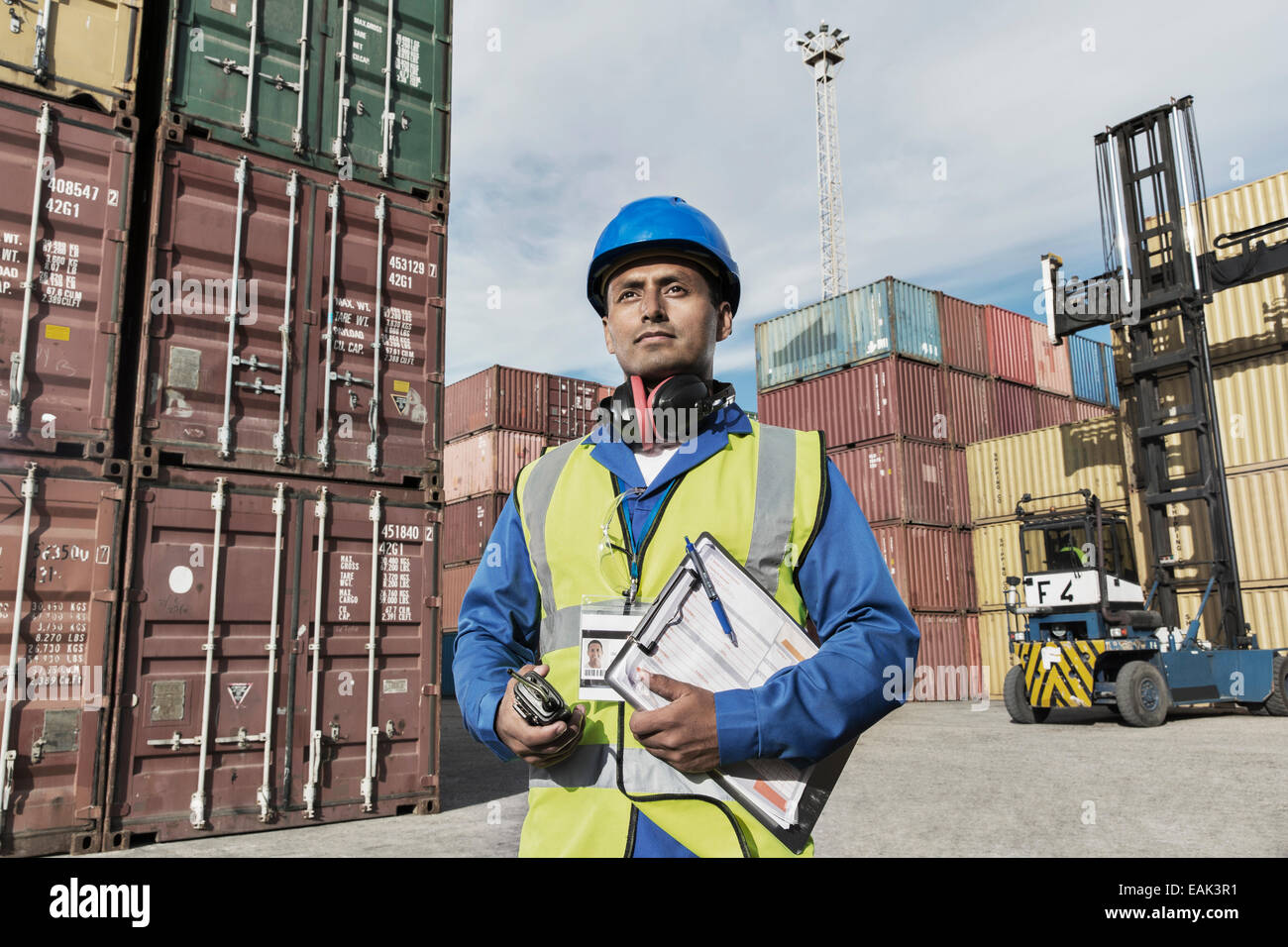 Worker holding clipboard near cargo containers Stock Photo