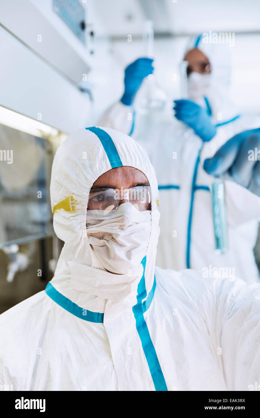 Scientist in clean suit examining test tube in laboratory - Stock Image