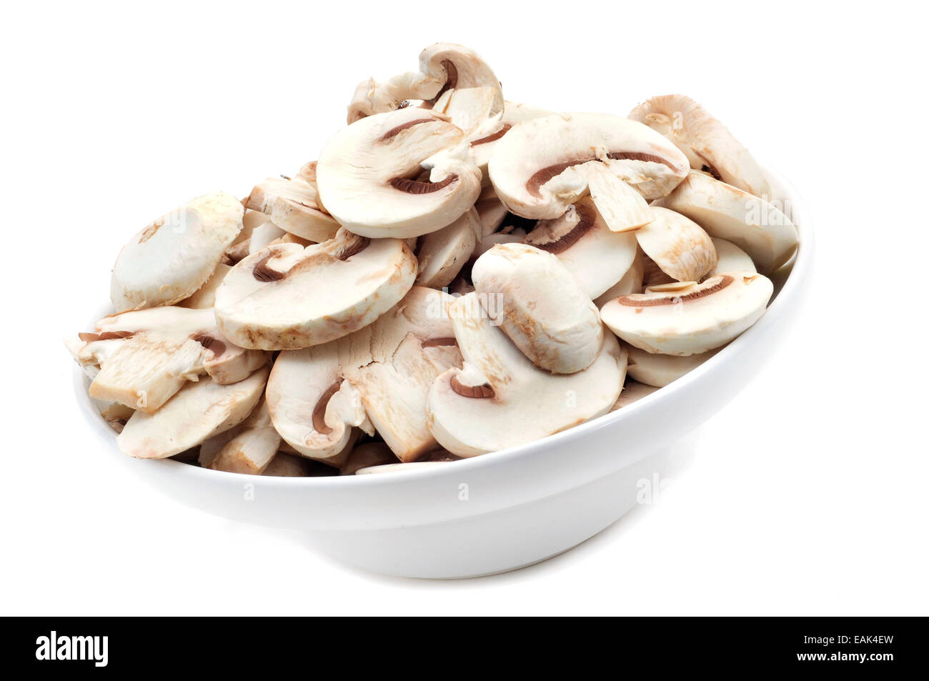 a bowl with sliced raw mushrooms on a white background - Stock Image