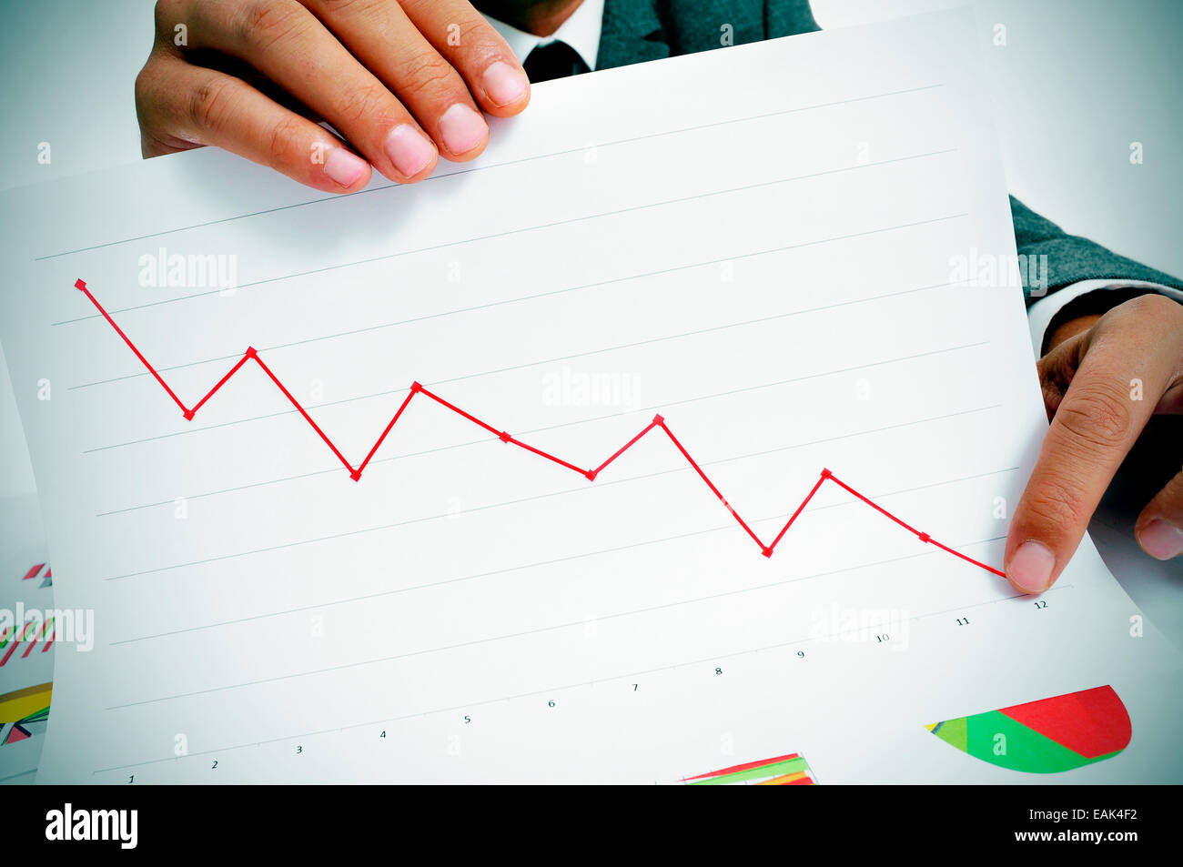man wearing a suit sitting in a table showing a graph of economic losses Stock Photo