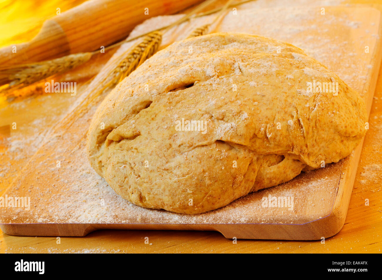 closeup of a homemade dough on a wooden table with some wheat ears and a rolling pin - Stock Image