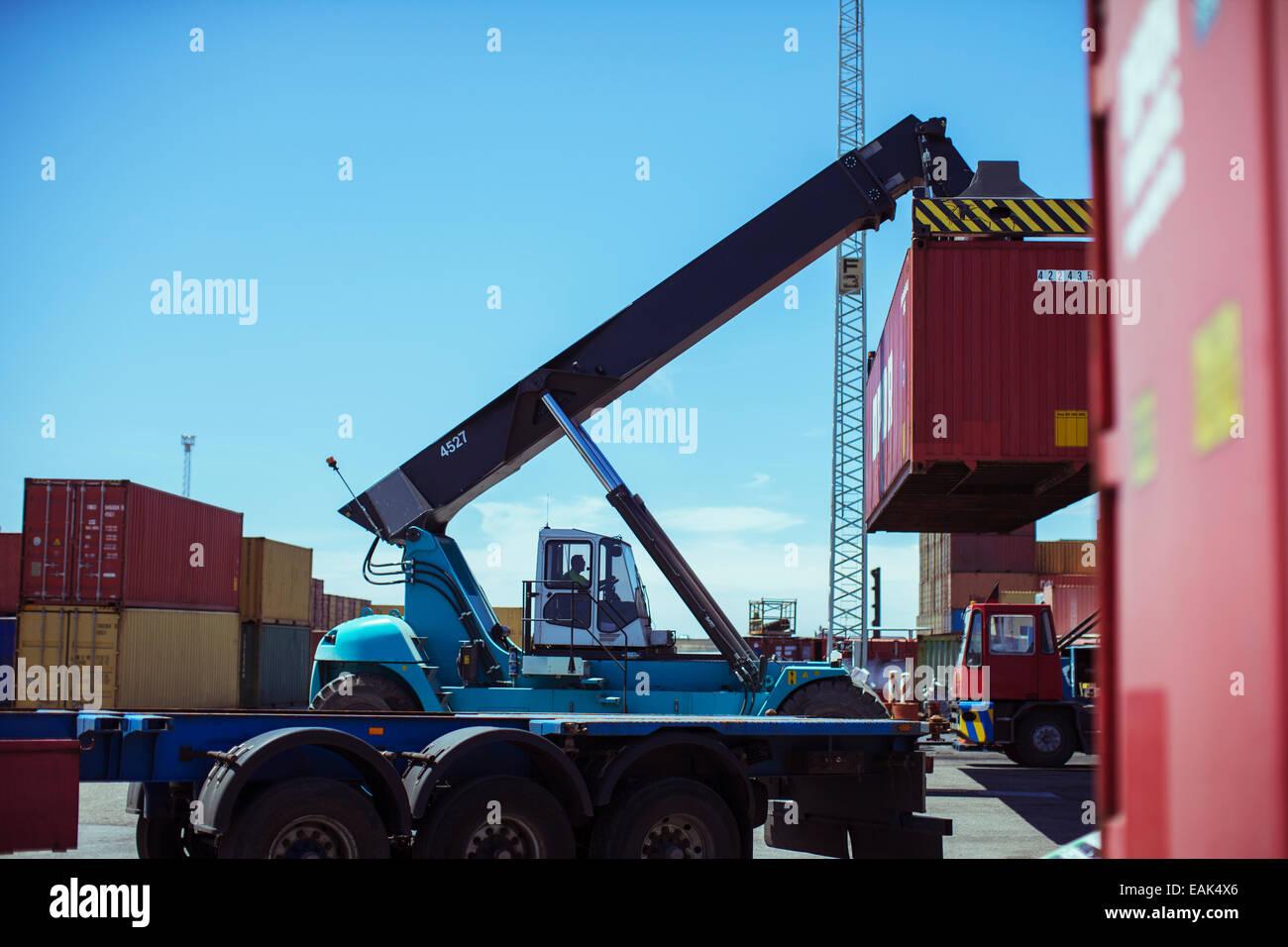 Crane lifting cargo container - Stock Image