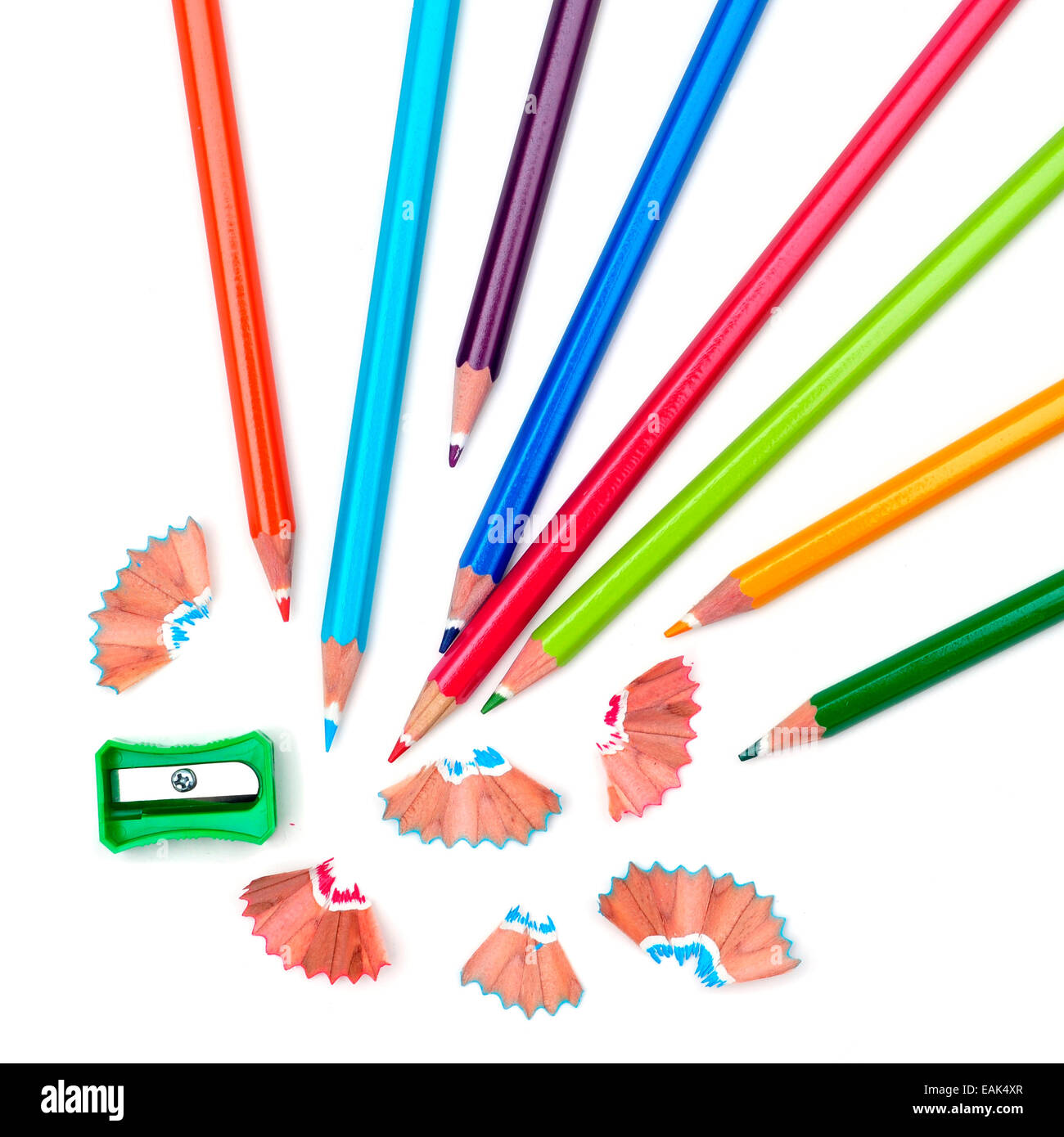 some colored pencils of different colors and a pencil sharpener and pencil shavings on a white background - Stock Image