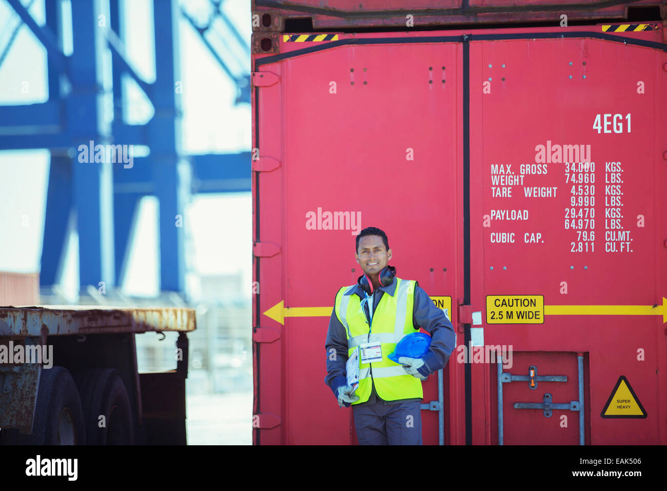 Worker smiling near cargo container - Stock Image