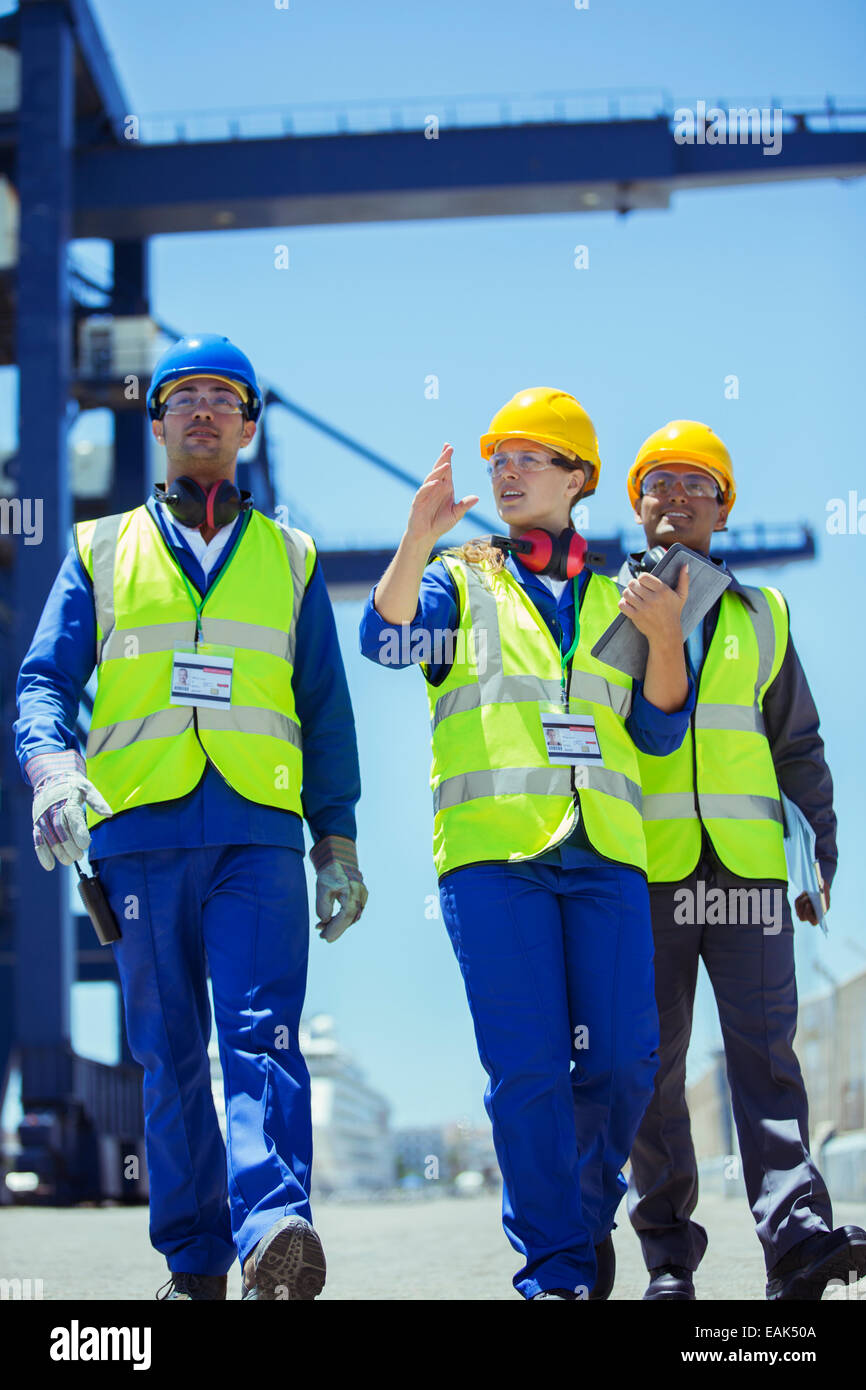 Workers and businessman talking near cargo crane Stock Photo