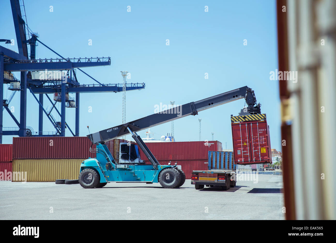Crane lifting cargo container onto truck - Stock Image