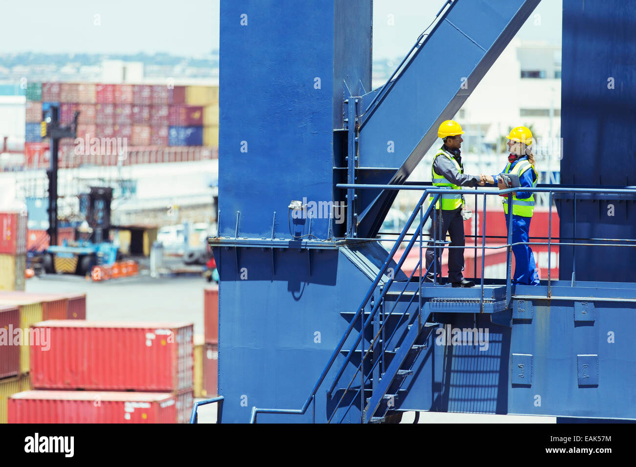Worker and businessman shaking hands on cargo crane - Stock Image