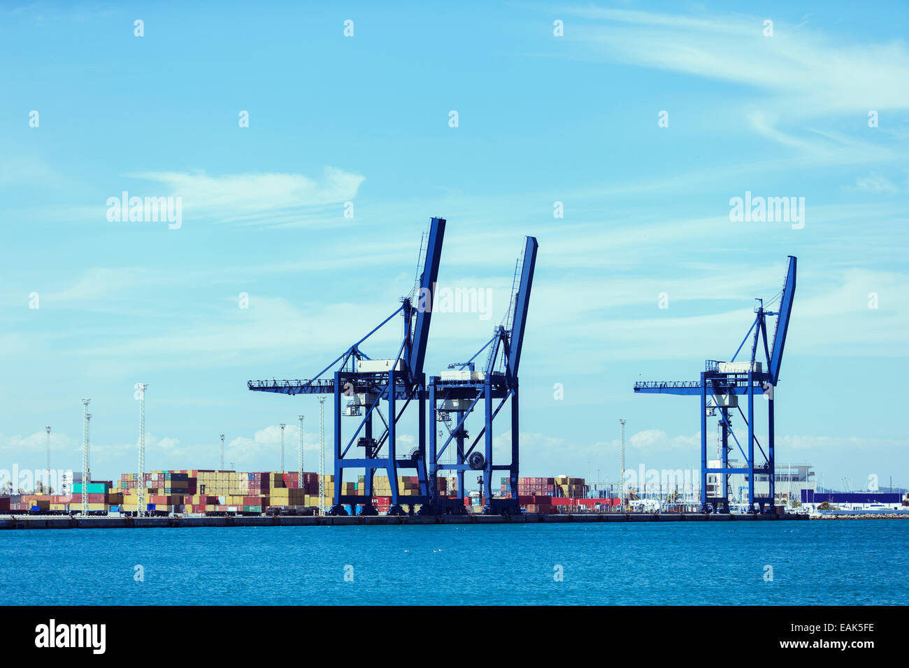 Cranes and cargo containers at waterfront - Stock Image