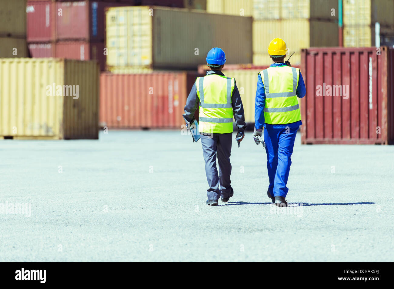 Workers walking near cargo containers - Stock Image