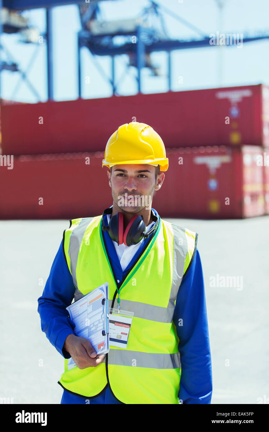 Worker carrying clipboard near cargo containers - Stock Image