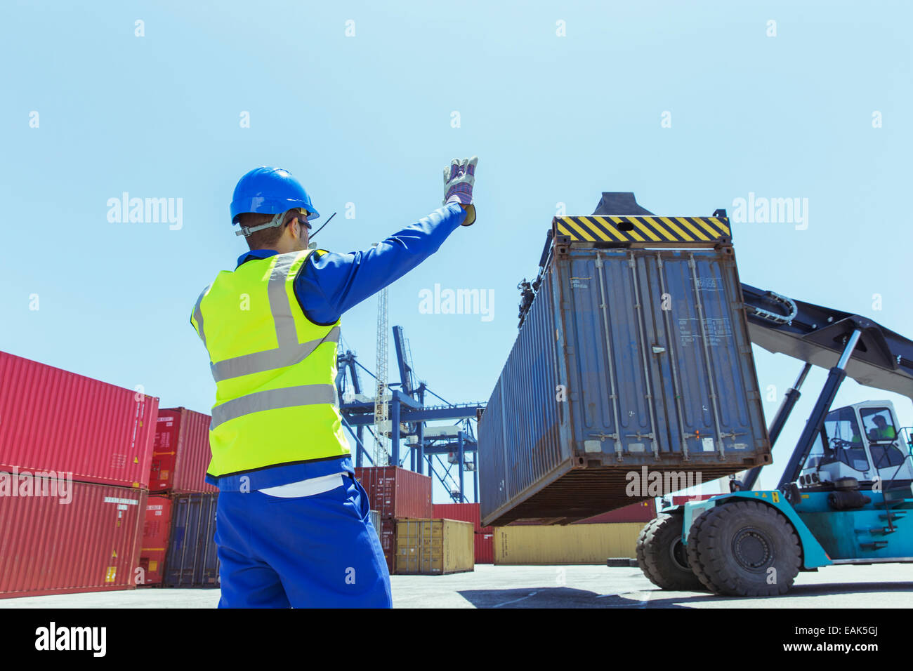 Worker directing crane carrying cargo container - Stock Image