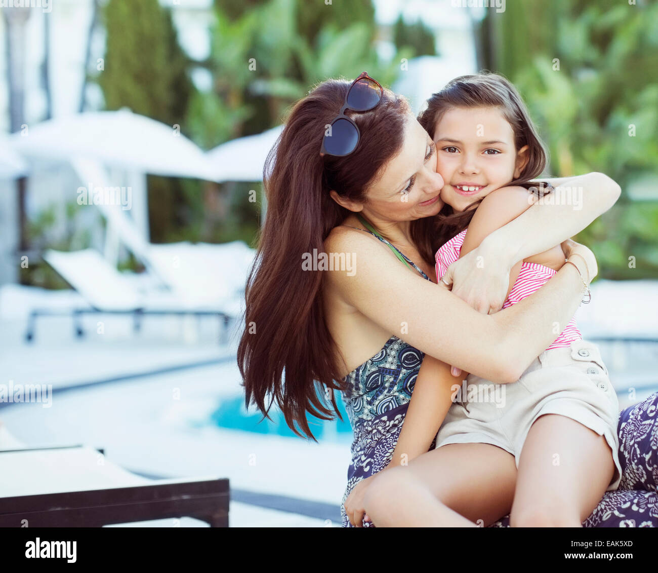 Mother embracing her daughter on poolside - Stock Image