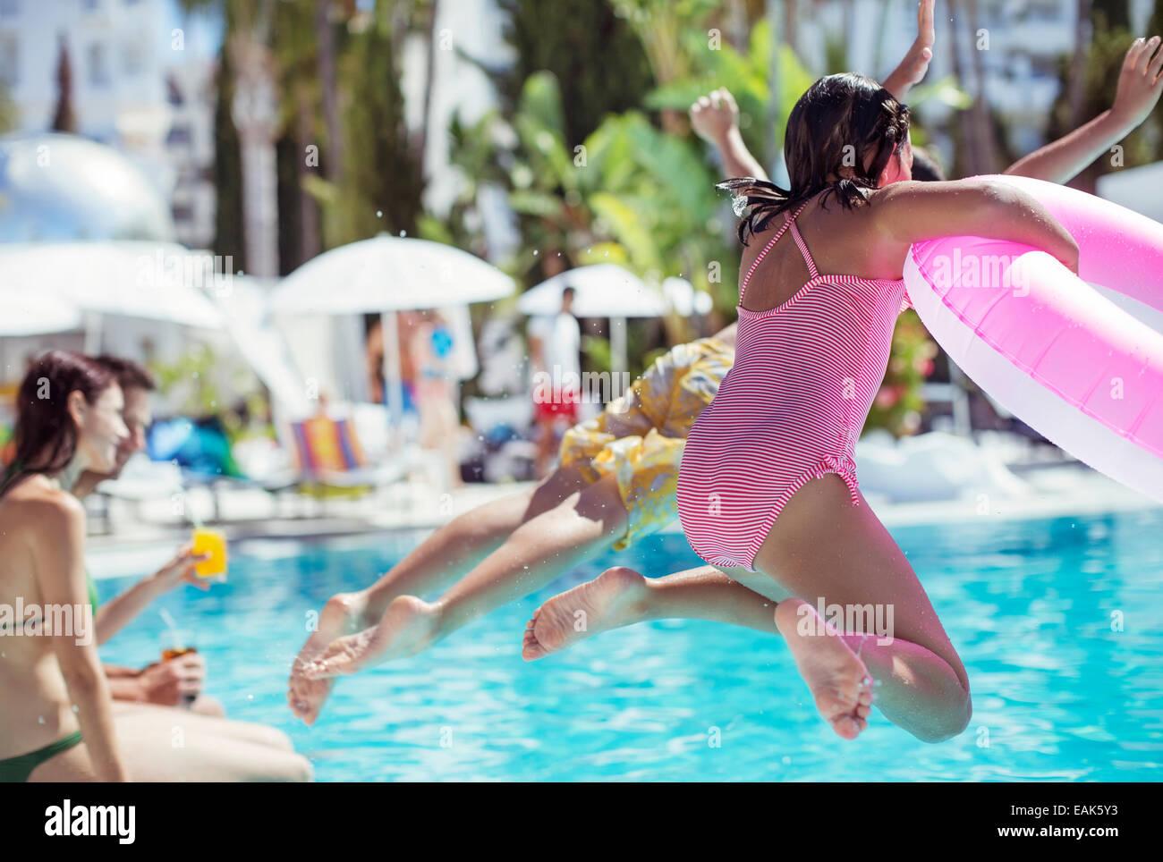 Children jumping into resort swimming pool Stock Photo
