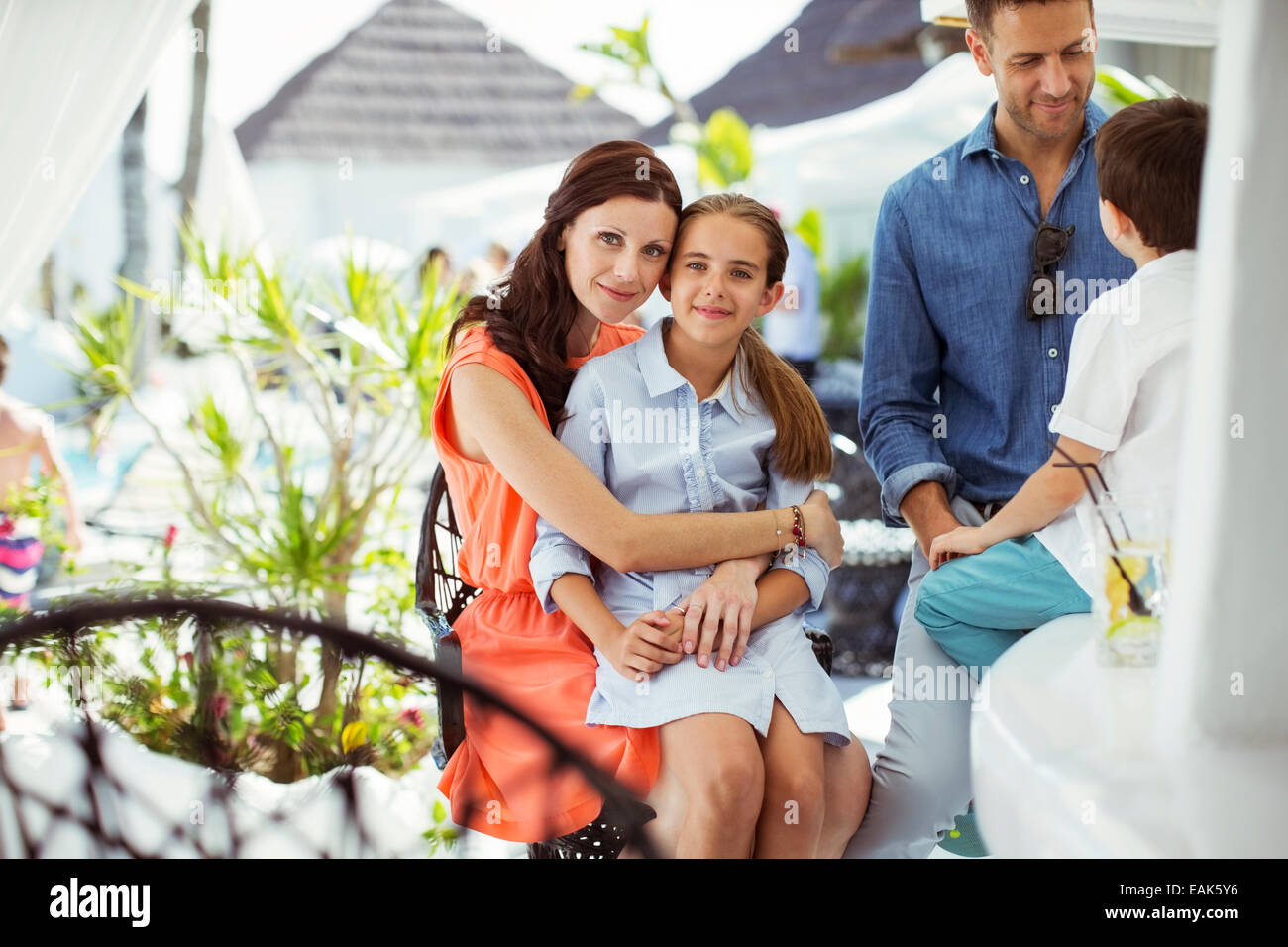 Happy family with two children relaxing in resort pool area - Stock Image