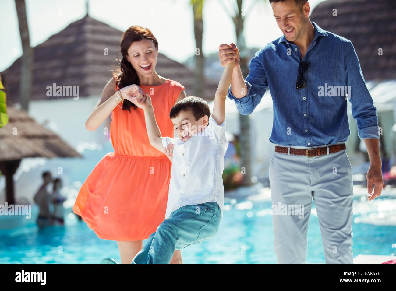Little boy having fun with his parents by swimming pool - Stock Image