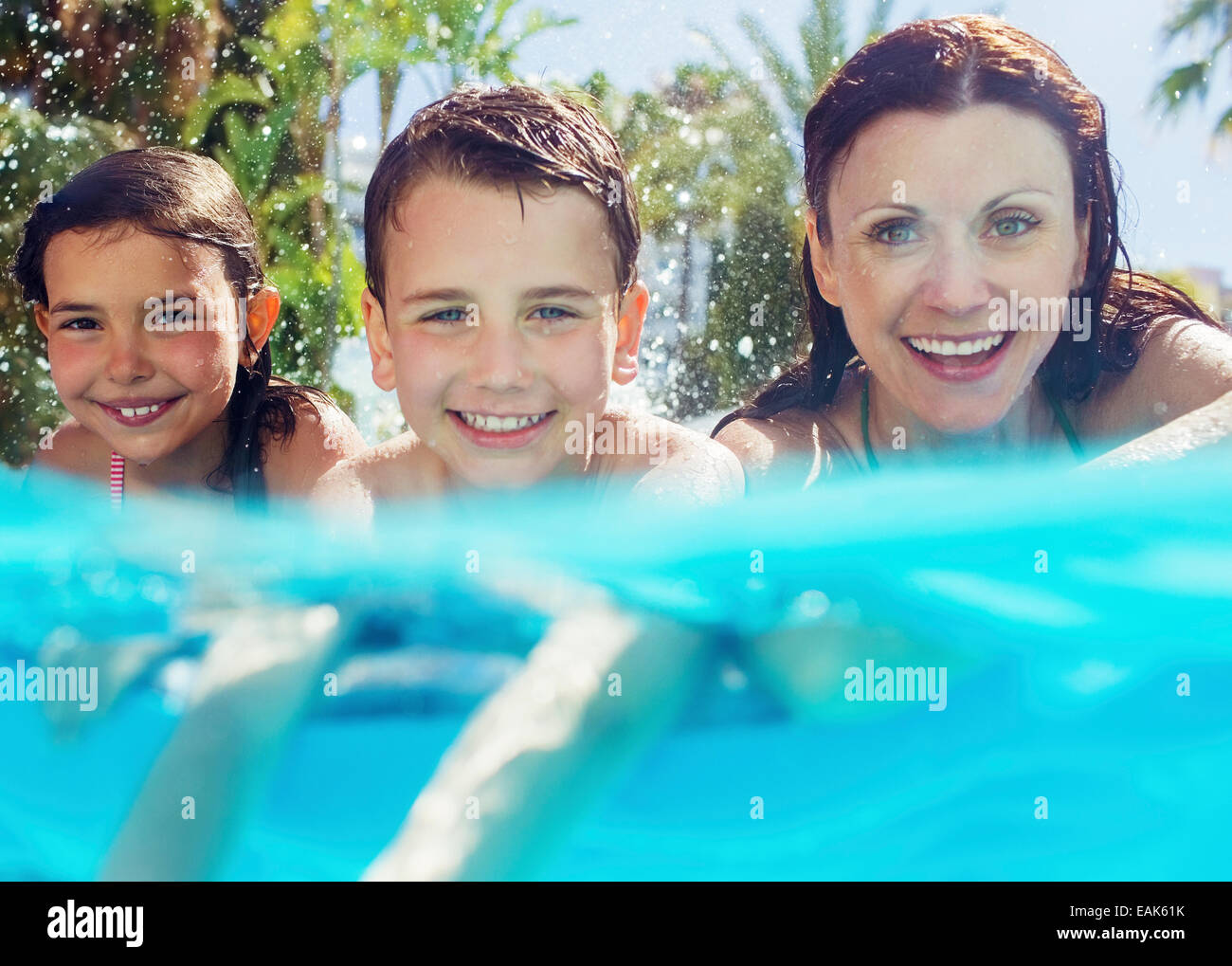 Portrait of mother with her two children in swimming pool - Stock Image