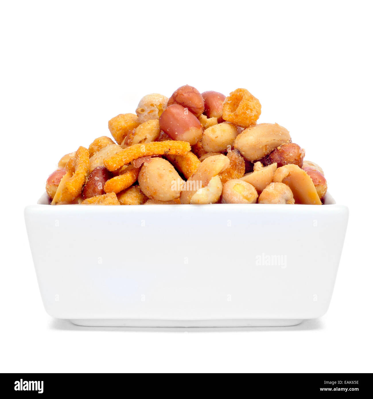 a bowl with mixed nuts, such as roasted and salted peanuts, almonds or chickpeas on a white background - Stock Image