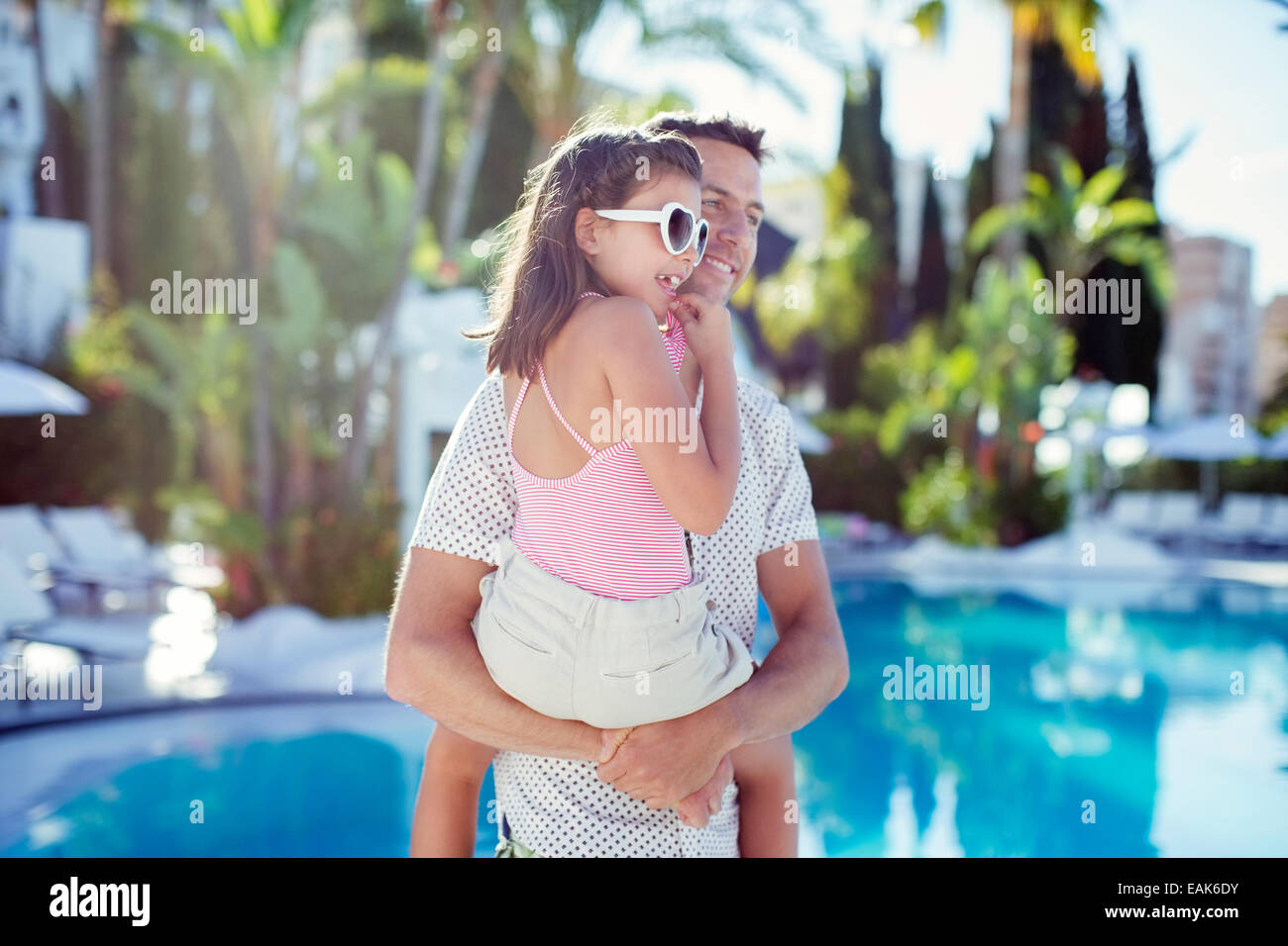 Man carrying his daughter by swimming pool - Stock Image