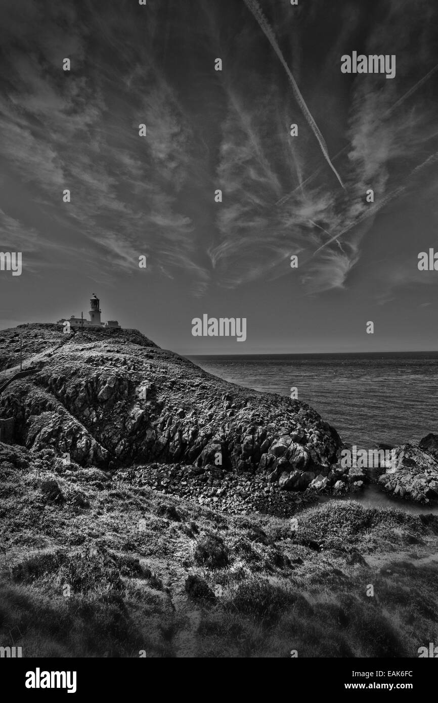 A black and white photograph of a landscape incorporating a lighthouse shot in Pembroke, Wales, UK - Stock Image