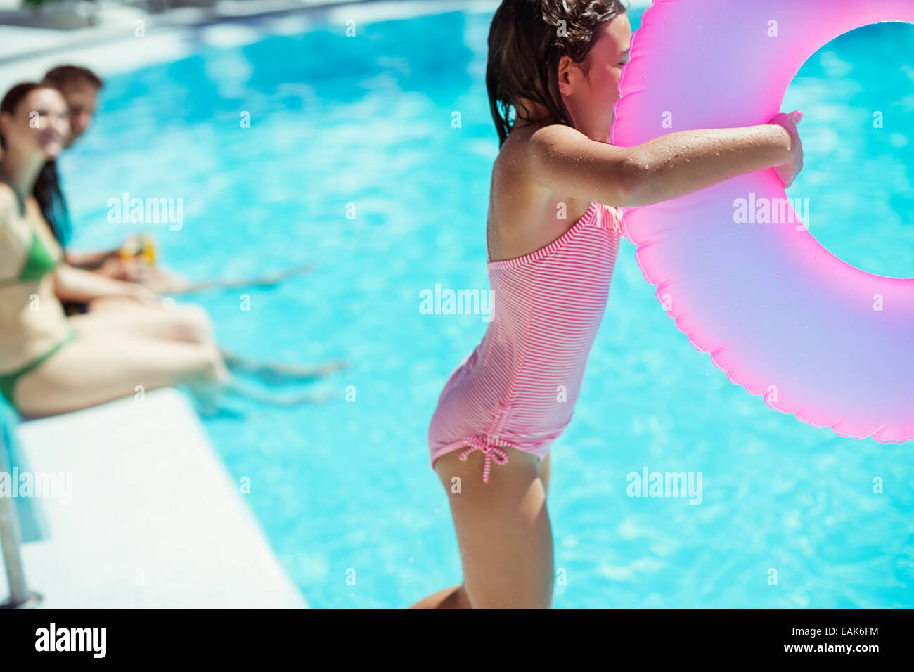 Girl with pink inflatable ring jumping into swimming pool - Stock Image