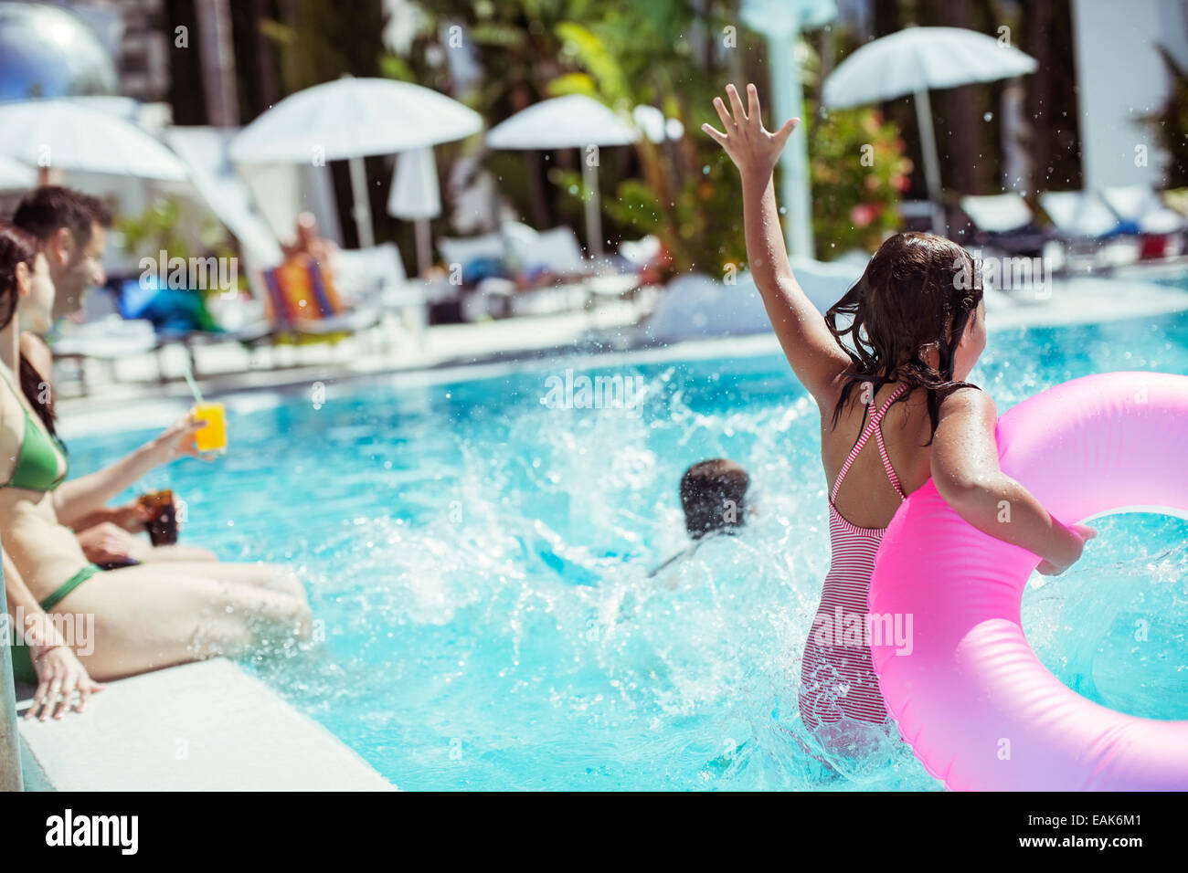 Girl with pink inflatable ring jumping into swimming pool, family in background - Stock Image