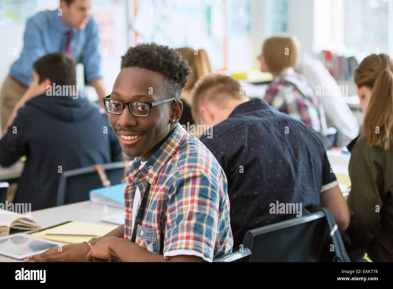 Smiling and confident students with teacher in classroom - Stock Image