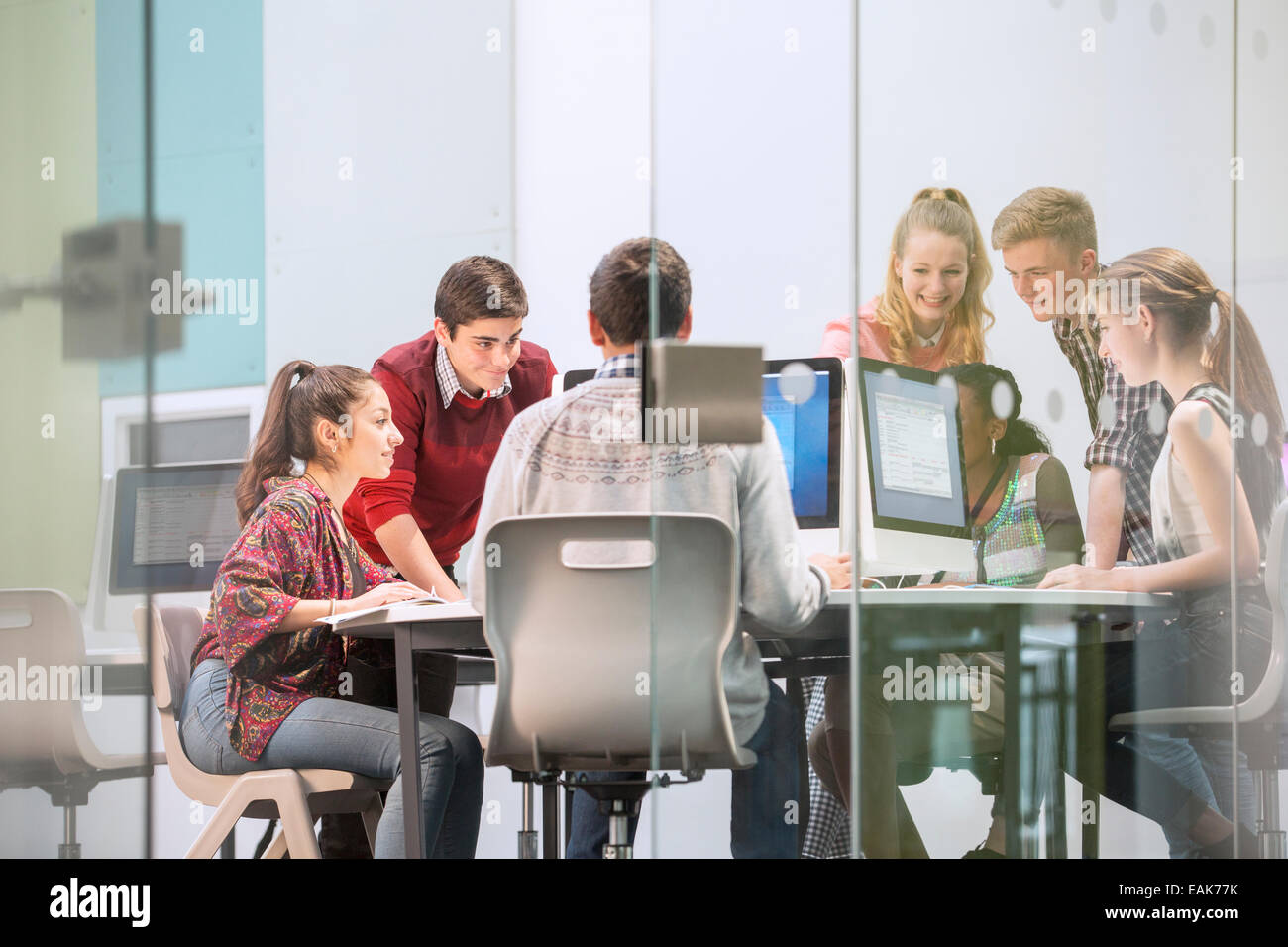 Students working with computers behind glass door Stock Photo