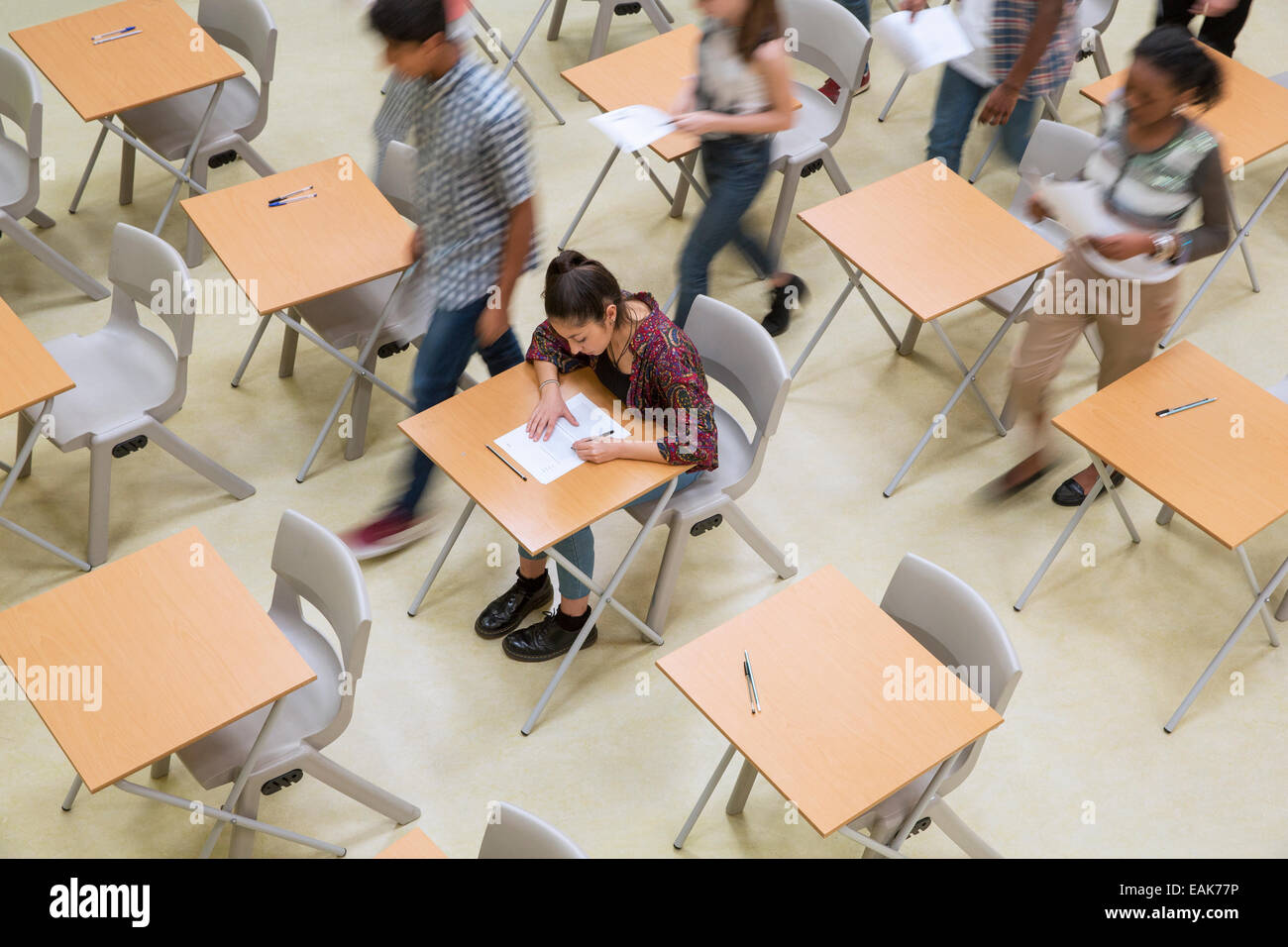 Elevated view of students writing their GCSE exam in classroom - Stock Image