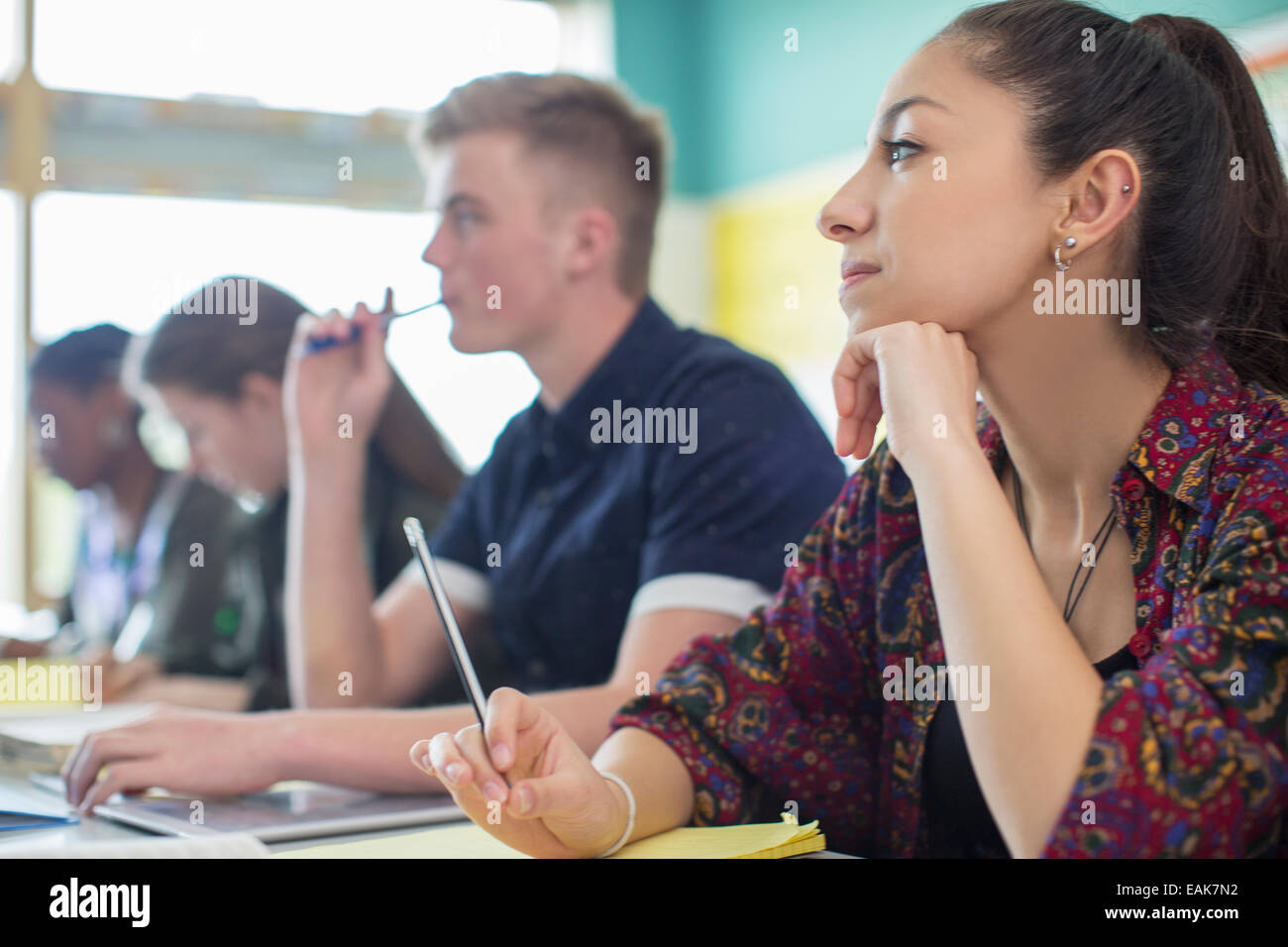 Female student contemplating in classroom - Stock Image