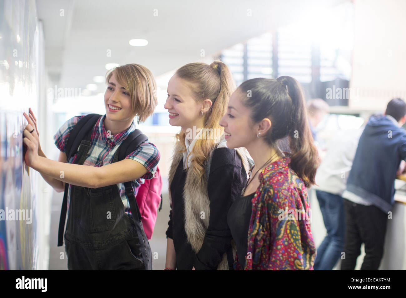 Three female students checking exam results in school corridor - Stock Image