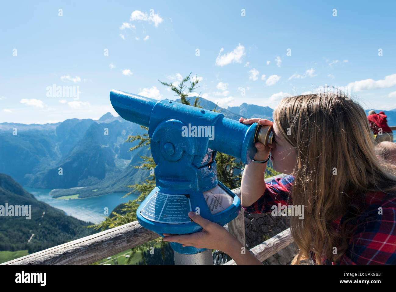 Young woman looking through a blue telescope, on Mt Jenner, Berchtesgaden, Bavaria, Germany - Stock Image