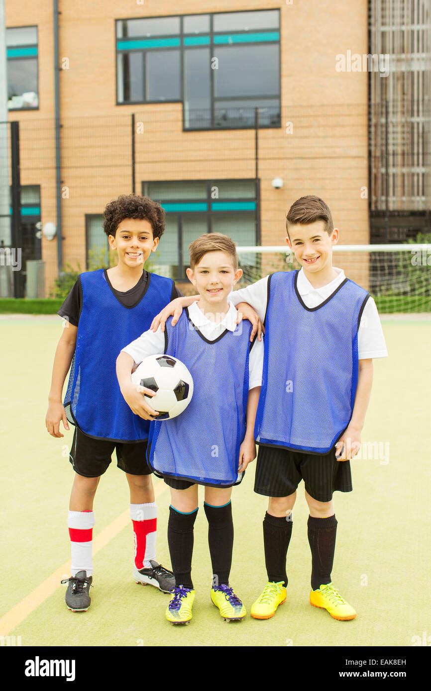 Portrait of three smiling boys wearing soccer uniforms and holding soccer ball in front of school Stock Photo