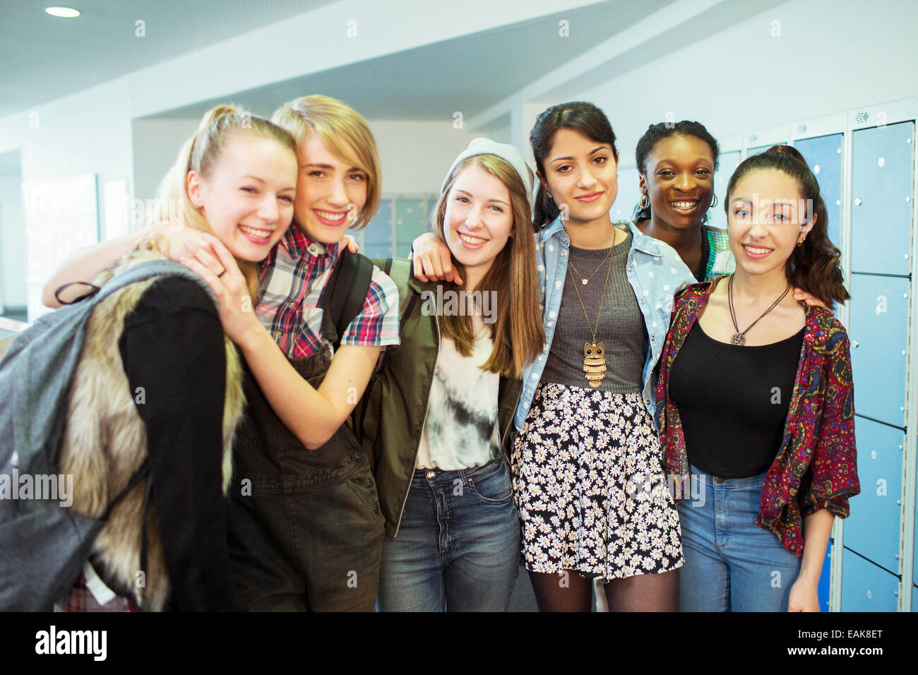 Group portrait of cheerful female students standing in locker room Stock Photo