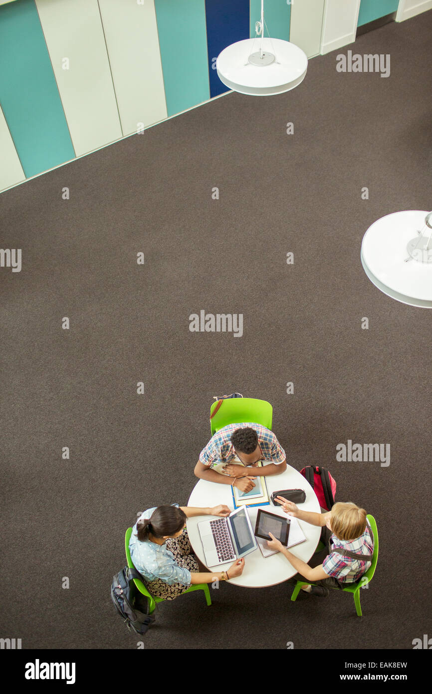 Overhead view of student doing homework, using laptop and digital tablet - Stock Image