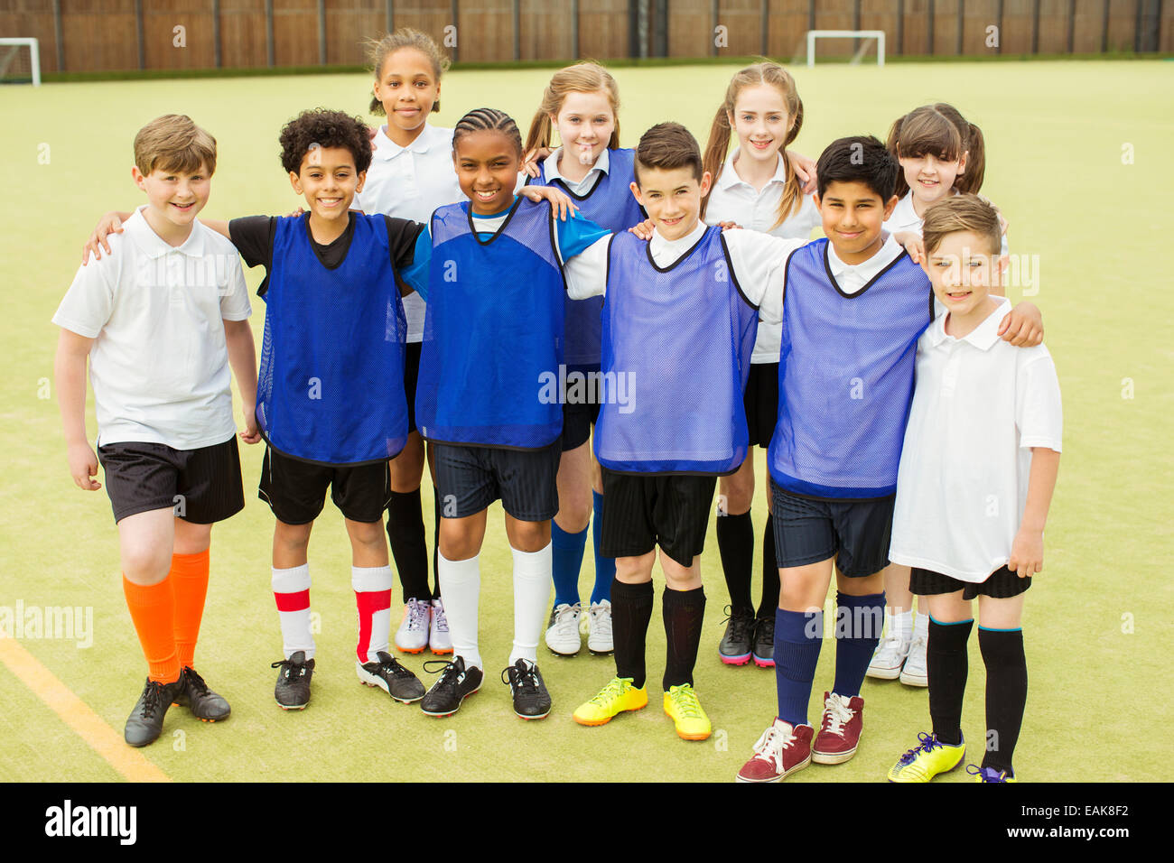 Group portrait of children wearing sport uniforms standing in school gym Stock Photo