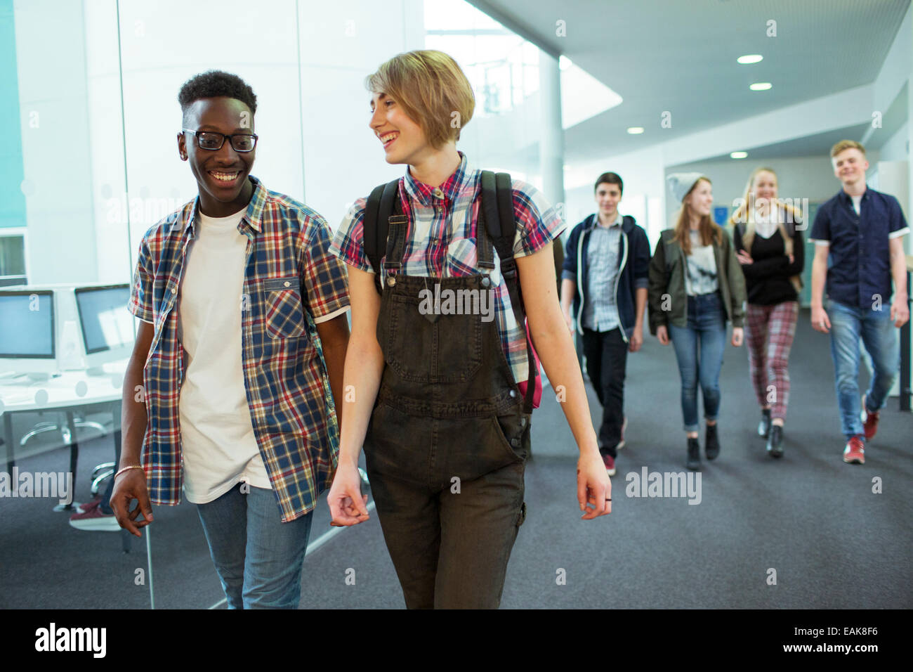 Group of students walking in corridor and smiling - Stock Image