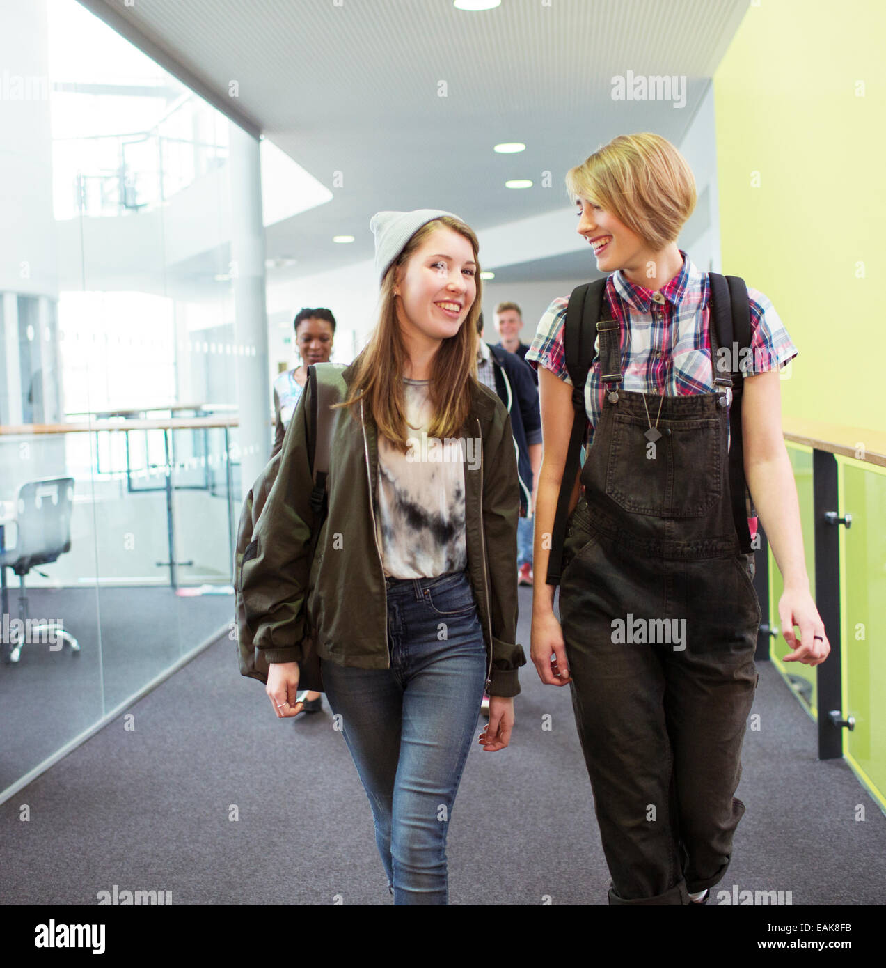 Group of cheerful students walking in corridor - Stock Image